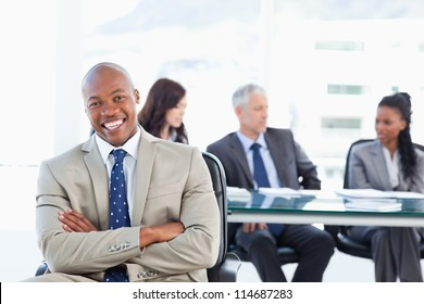 Young executive laughing while crossing his arms and sitting in front of his team