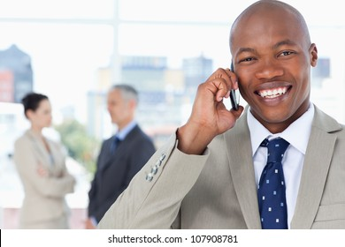 Young executive laughing while using his mobile phone