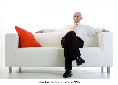 A young executive leans back, relaxing on the couch.