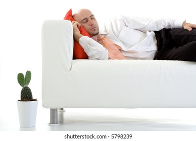 A young executive lying down on the couch, taking a nap.
