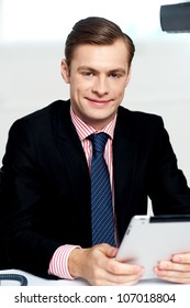 Young executive posing with tablet pc and smiling at camera