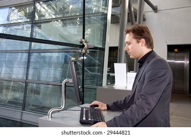 A young executive is standing and using the computer in the  in a business lounge