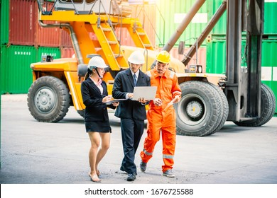 The young executive visits the container storage yard to inspect the work with the personal secretary and foreman. Business and  Teamwork concepts, Transportation and Logistics concepts.