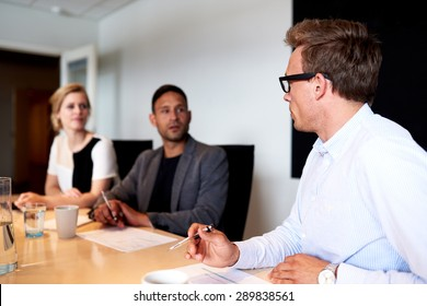 Young executives facing eachother during a meeting in conference room