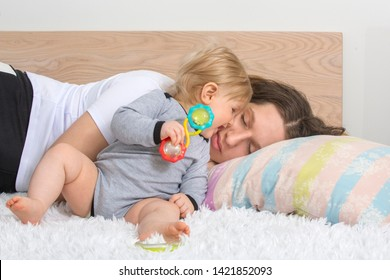 Young exhausted taking a nap mother got asleep while holding her newborn not sleeping baby at home bedroom. Motherhood concept.
