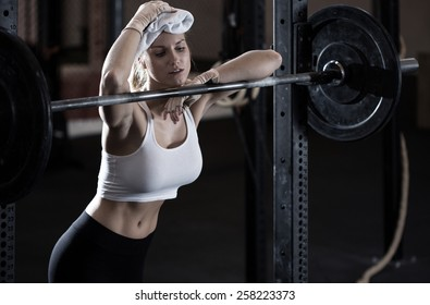 Young exhausted weightlifting girl after training