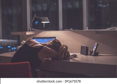 Young exhausted  woman sleeping at the desk in her room or office with french windows  in the dark at the lamp.Studies late at night.Staying up late. Overworking.Meeting deadline.