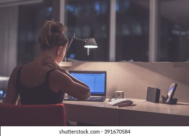 Young exhausted,depressed,concentrated woman sitting in her room or office with french windows  in the dark at the lamp.Studies late at night.Staying up late. Overworking.Feeling pain in the neck