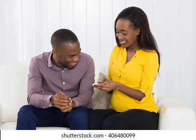 Young Expectant Couple Sitting On Sofa Looking At Pregnancy Test