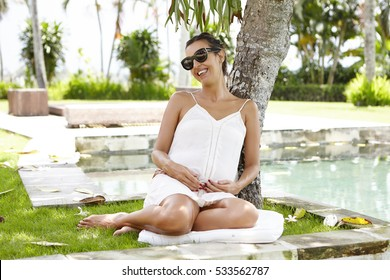 Young expectant mother in shades having rest under tree during nice walk in hotel garden on sunny day. Pregnant female smiling happily, touching her belly while refreshing herself near water
