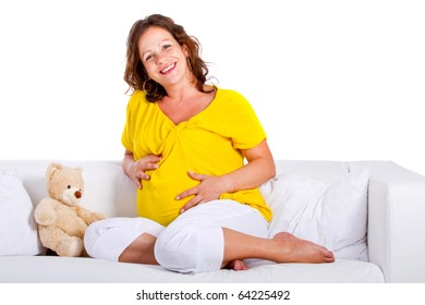 Young expecting mother is sitting on a couch at home. Highkey image over pure white background.