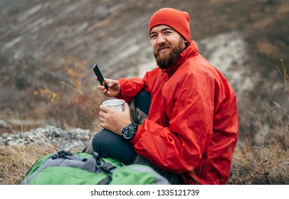 Young explorer bearded man drinking tea or coffee in mountains. Traveler man wearing red clothes holding in hands a mug of tea, and browsing on Internet via his smart phone after hiking in moutain.