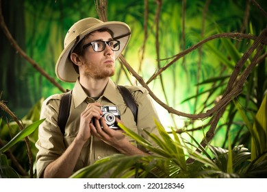 Young explorer in the jungle taking pictures with vintage camera,