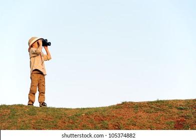Young explorer looking with binoculars in safari clothing.