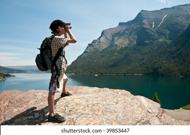 young explorer looks at the scenic view through binoculars at Glacier National Park