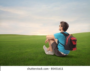 Young explorer sitting on a green meadow