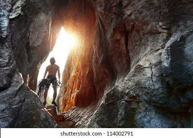 Young explorer standing in a cave with climbing equipment ready for action