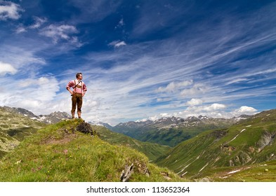 Young explorer in traditional clothing stands proud on top of a mountain in the Swiss Alps on a sunny summer day
