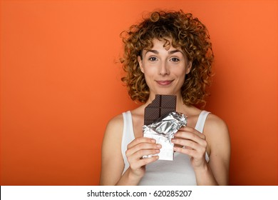 young expressive curly woman with bar of chocolate on orange background