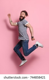 Young expressive hipster man posing while jumping on pink background and looking at camera.