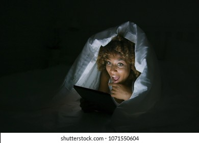 Young expressive model lying in bed covered with blanket and posing excitedly while watching tablet in night dark.