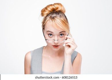 Young extremely shocked woman in glasses and vest on grey background. Portrait of dumbfounded woman looking surprisingly at camera.