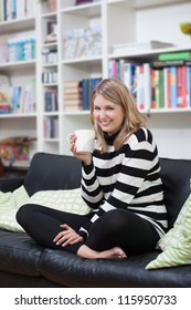 Young fair-haired woman drinks a coffee on the couch
