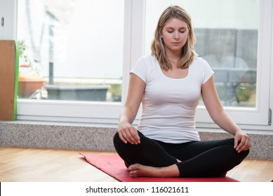 Young fair-haired woman meditates on a gymnastic mat