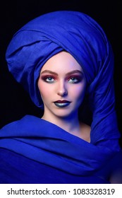 Young fair-skinned blue-eyed girl in a bright blue berber turban on a black background. Female portrait in moroccan style with creative make up.