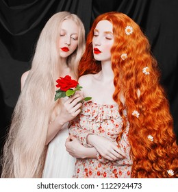 Young fairy woman with very long hair in flower dress on black background. A beautiful girl with pale skin. Renaissance fairy princess with a red rose in hands. Two sisters.
