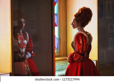 Young fairytale renaissance queen with hairstyle on light background.  Fairytale queen in red dress. Edwardian duchess.