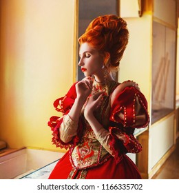 Young fairytale rococo queen portrait with historical hairstyle on light background. Renaissance princess with red hair. Rococo queen in red historical dress. Edwardian duchess with ring on finger.
