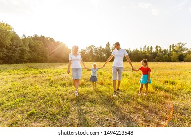 young familiy running through a yellow field