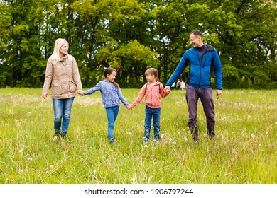 young familiy are walking through a green field