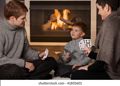 Young family with 4 years old kid playing card game at home in a cold winter day.