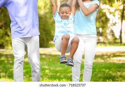 Young family with adopted African American boy having fun outdoors