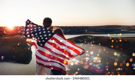 Young family with the American flag behind them at sunset celebrates Independence Day.  USA celebrate 4th of July. Patriotic holiday.