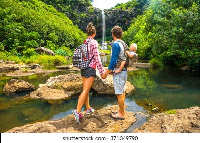 a young family with a baby enjoys the view of a beautiful waterfall on the island of Mauritius