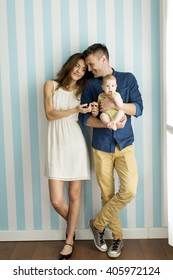 Young family with a baby standing by the wall