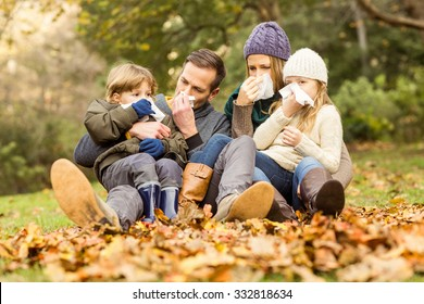 Young family blowing their nose on an autumns day
