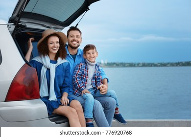 Young family with boy sitting in car trunk near river
