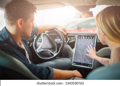 Young family buying first electric car in the showroom. Attractive couple chooising a way on electronic dashboard in modern electric hybrid vehicle before test driving. Auto trends and innovation