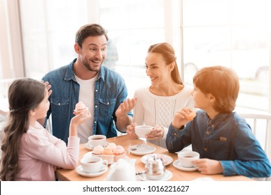 A young family came together in a cafe. Mom, dad, little daughter and son drink tea, eat cakes. They are happy together. Happy family lunch concept.