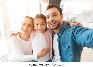 A young family came together in a cafe. Mom, dad and little daughter drink tea, eat cakes. They are happy together. Happy family lunch concept. Family selfie concept.