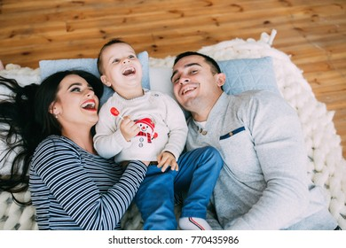A young family celebrates Christmas in a domestic homely atmosphere.