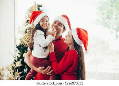 Young family celebrating Christmas at home.Happy young family enjoying their holiday time together.