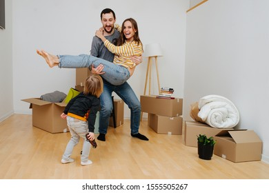 Young family celebrating moving into a new apartment, having fun together.. Room with empty walls, new beginning. Father holding mother on his arms, their son looks at them excited and surprised.