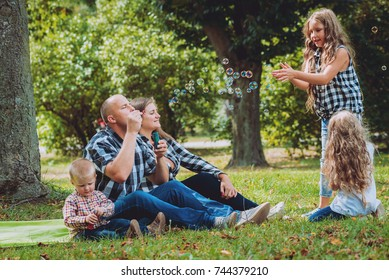 Young family with cheerful children in the park. Bubble blower