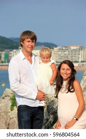 young family with a child by the sea, pregnant mother