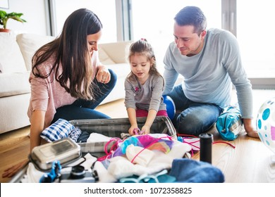 Young family with a child packing for holiday.